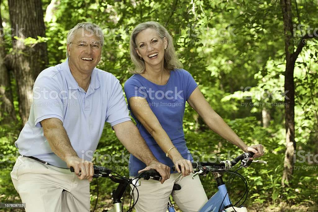 Couple on their bikes at a wooded park trail royalty-free stock photo