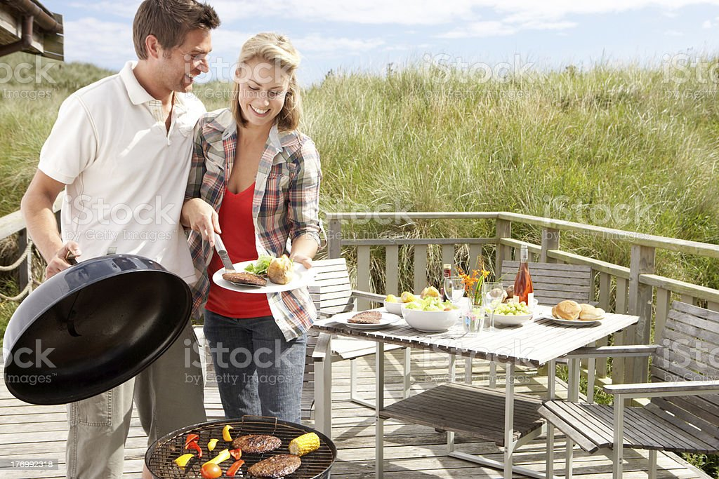 Couple on vacation having barbecue royalty-free stock photo