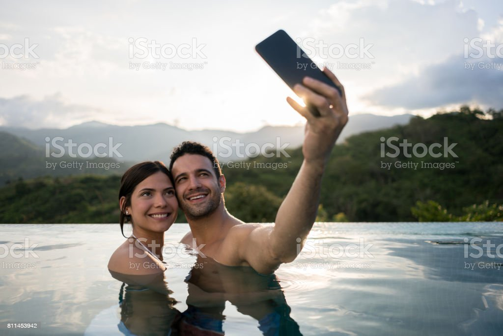 Couple on vacations taking a selfie in the pool stock photo