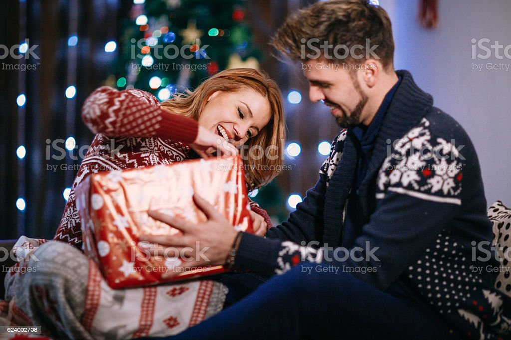 Couple opening presents before the tree the night Christmas stock photo