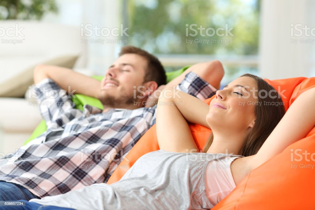 Couple or roommates relaxing at home stock photo