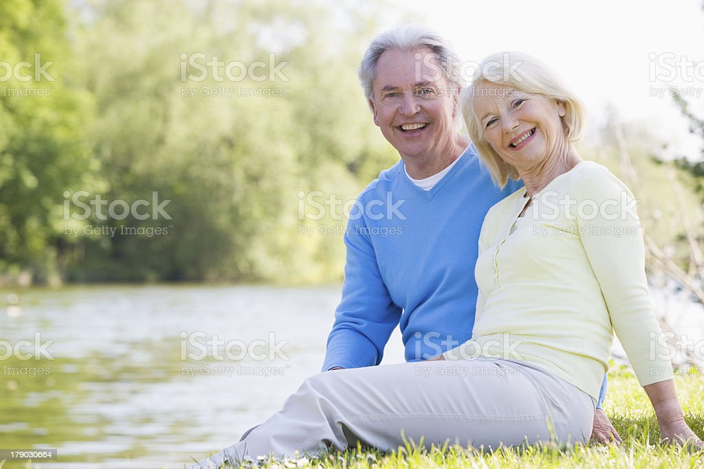 Couple outdoors at park by lake smiling stock photo