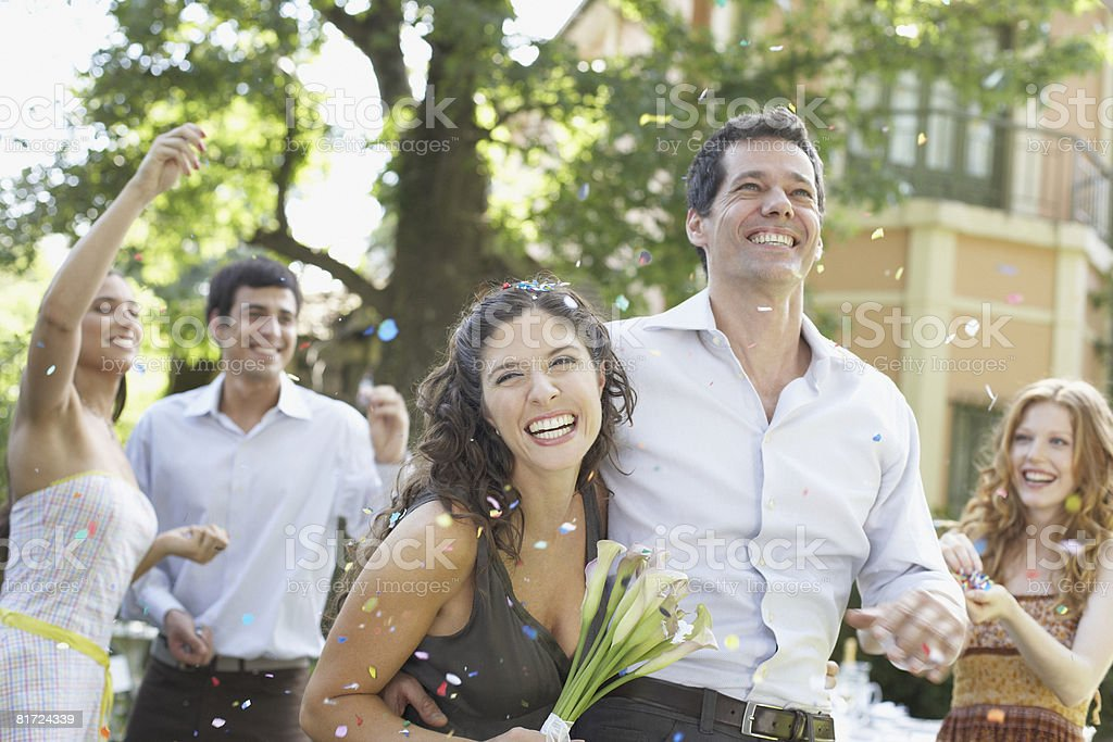 Couple outdoors at party carrying flowers and having confetti thrown at them royalty-free stock photo
