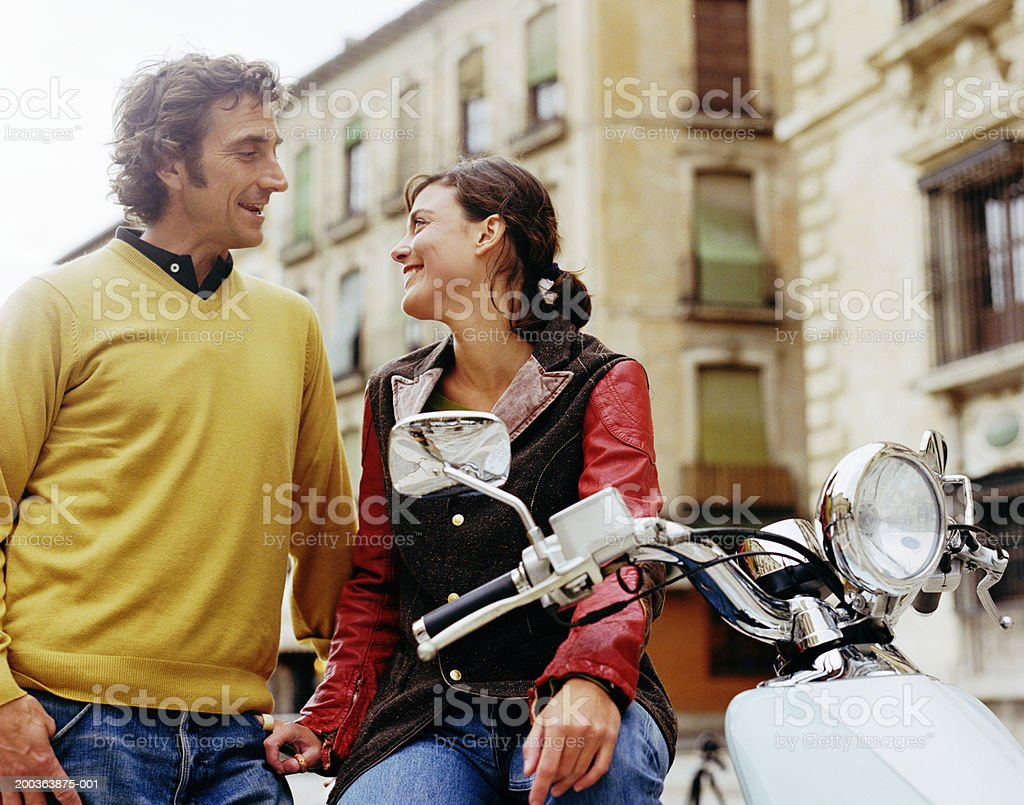 Couple outdoors by moped, smiling royalty-free stock photo