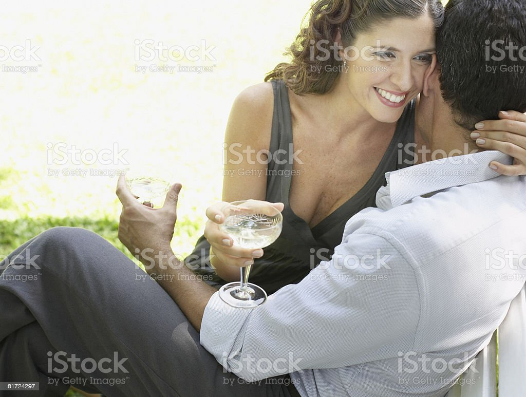 Couple outdoors with white wine embracing and smiling stock photo