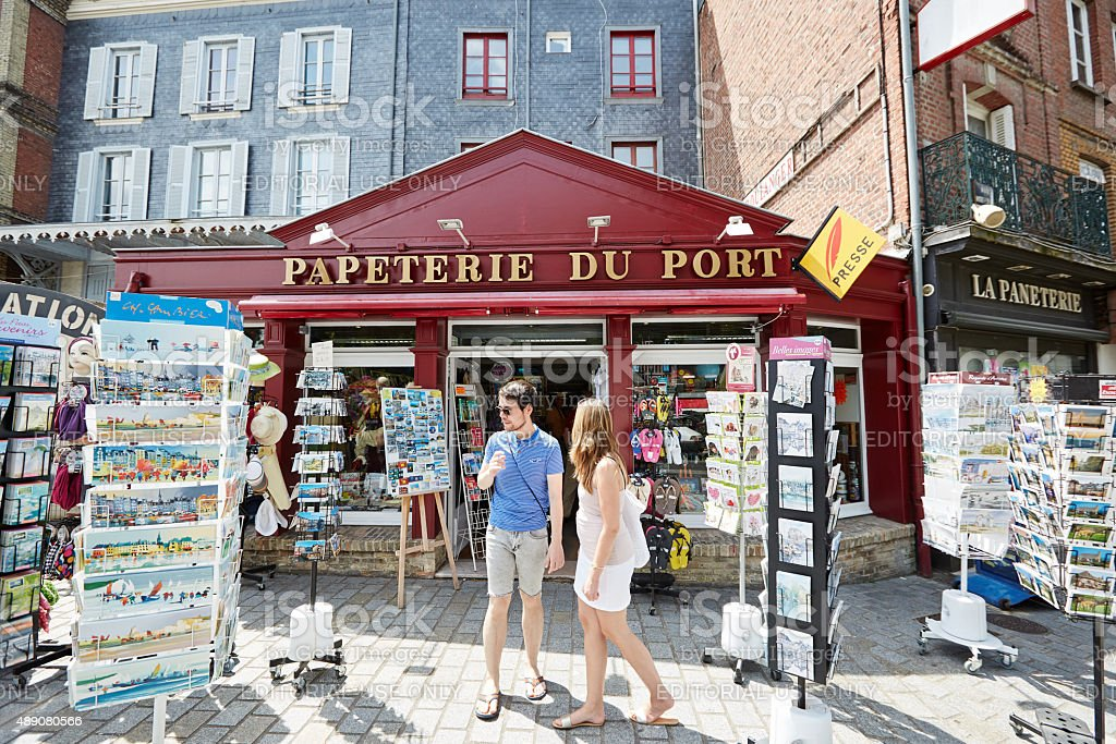 Couple outside newsagent shop on French harbourside stock photo