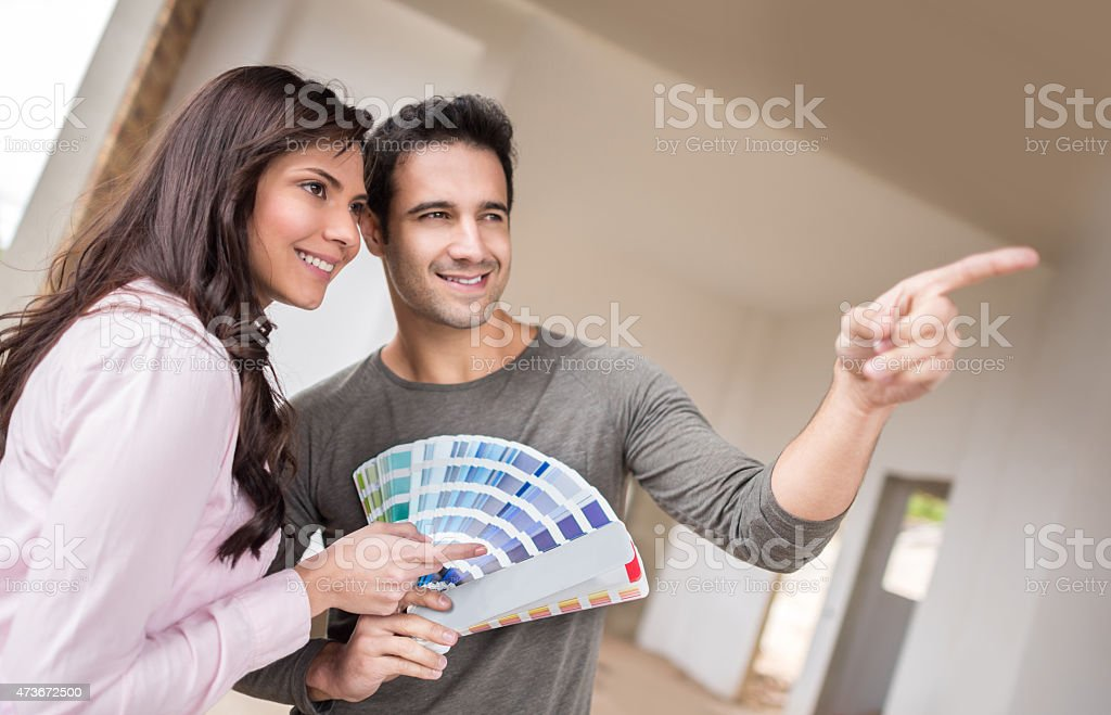 Couple painting the house and choosing the color stock photo