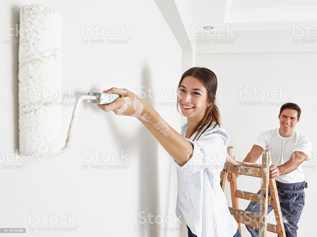 Couple painting wall using rollers stock photo
