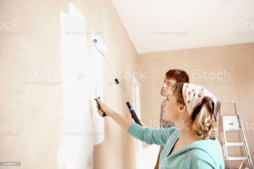 Couple Painting Wall With Paint Rollers stock photo