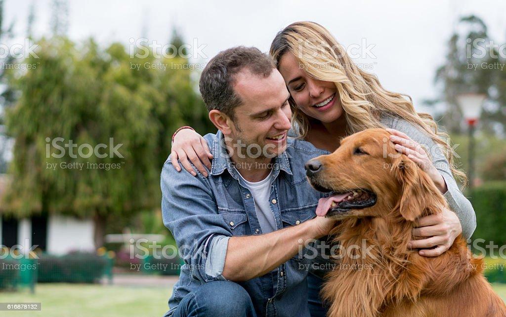 Couple pampering a beautiful dog stock photo