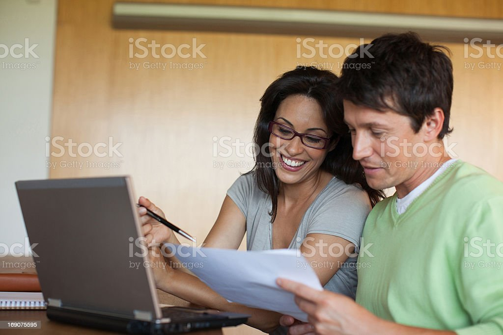 Couple paying bills on laptop together royalty-free stock photo