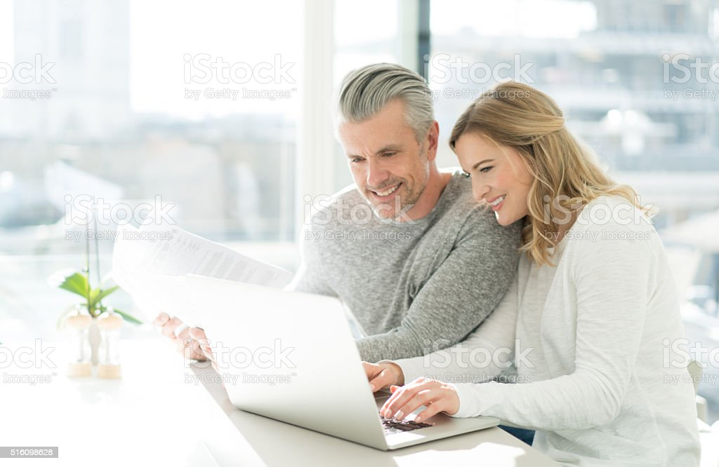 Couple paying bills online at home stock photo