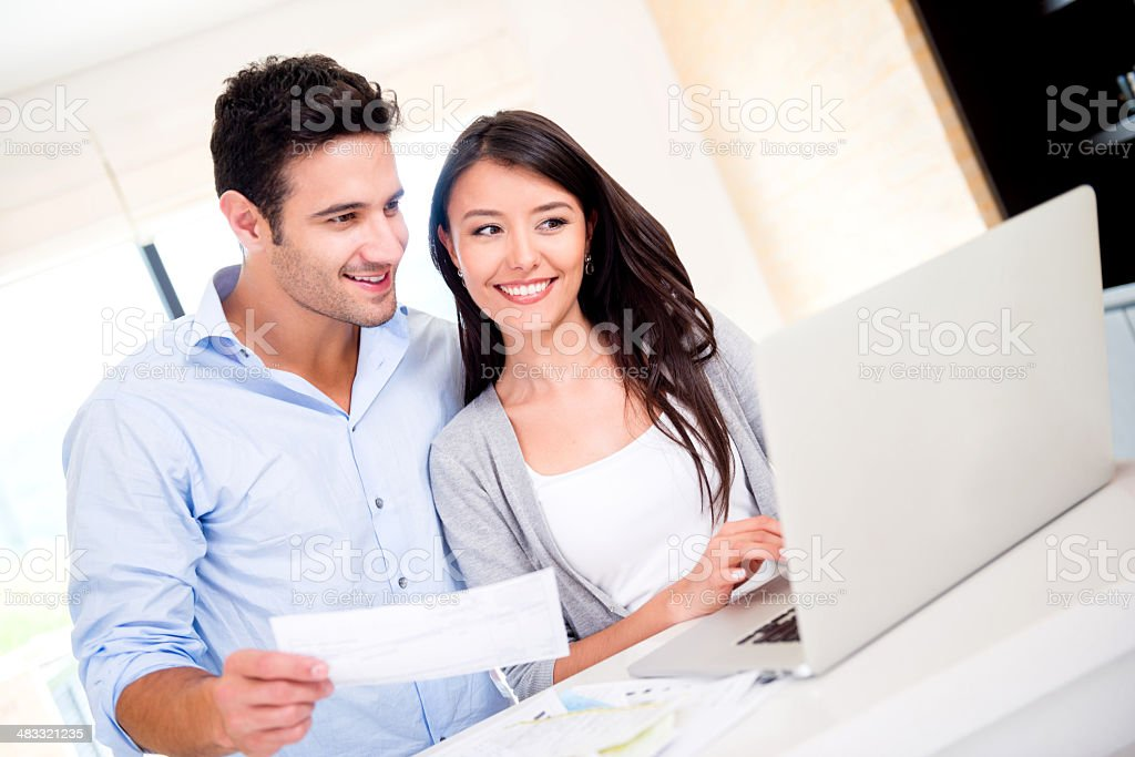 Couple paying bills online stock photo