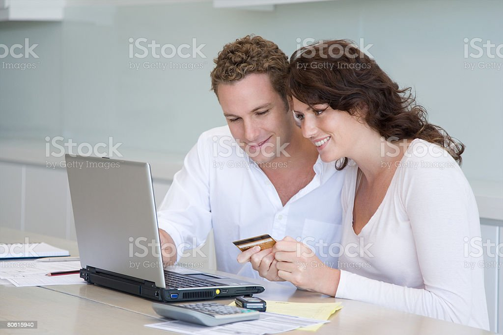 A couple paying bills online stock photo