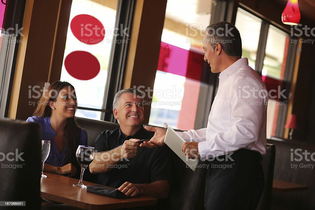 Couple Paying By Credit Card In Restaurant stock photo