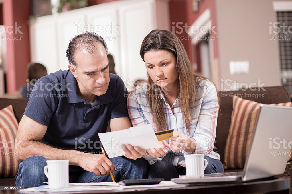 Latin descent man and woman work together to pay their monthly bills....
