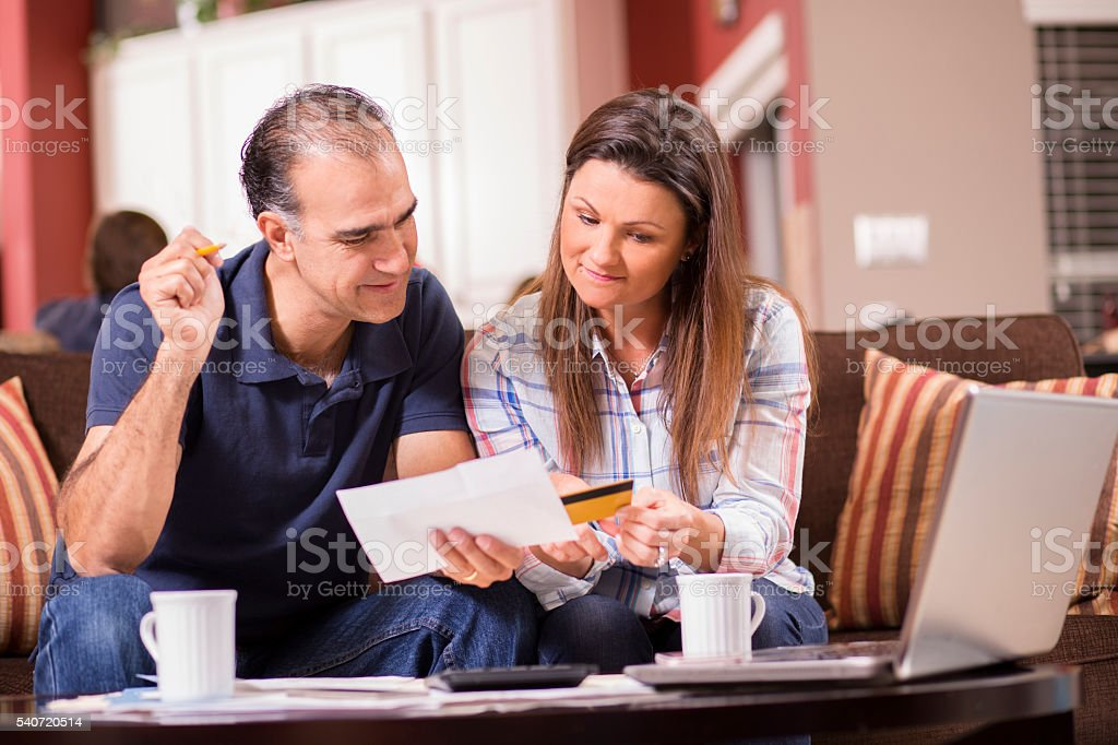 Couple paying monthly bills at home.  Credit card, laptop. stock photo