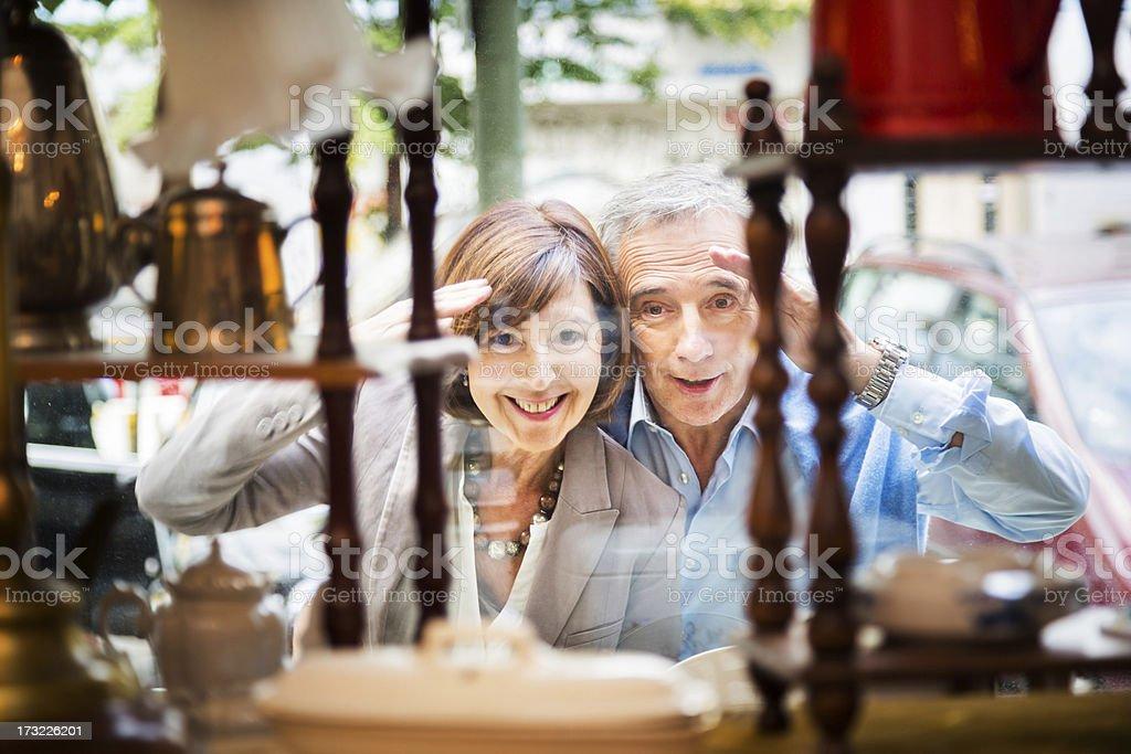 Couple Peeking Through Shopping Window royalty-free stock photo