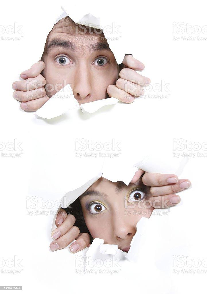couple peeping through hole in white paper stock photo