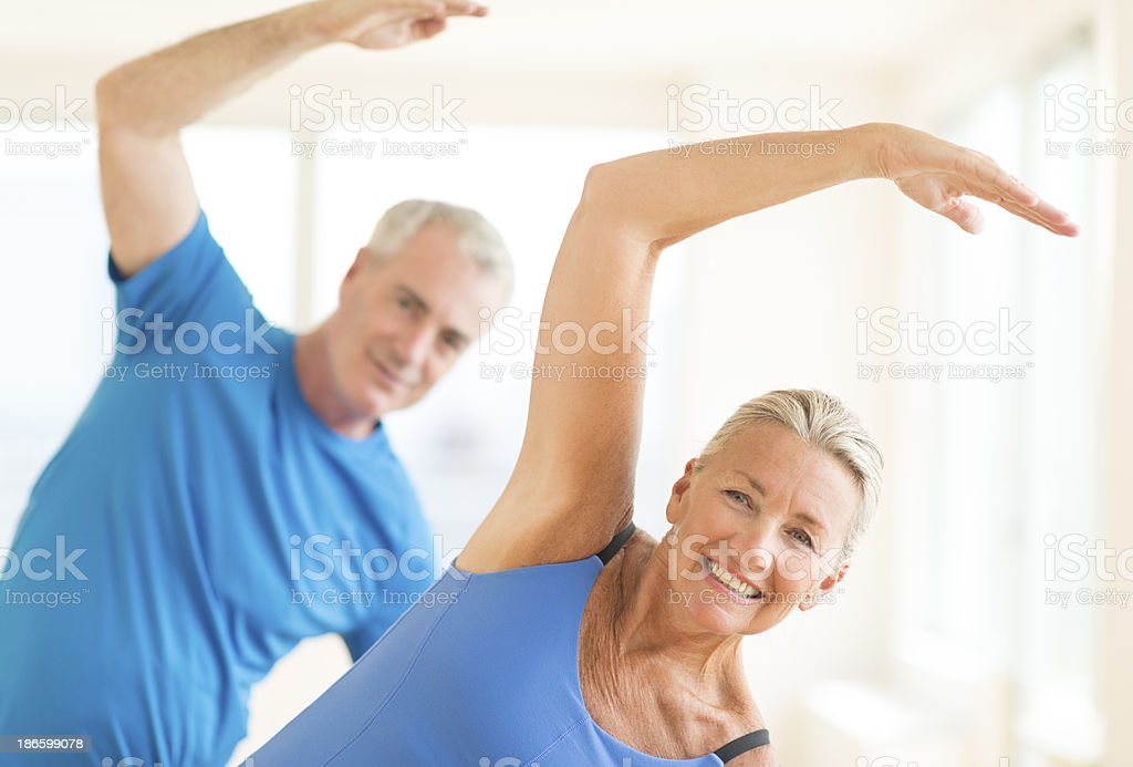 Couple Performing Stretching Exercise At Home stock photo