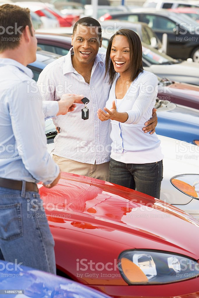 Couple picking up new car from salesman stock photo
