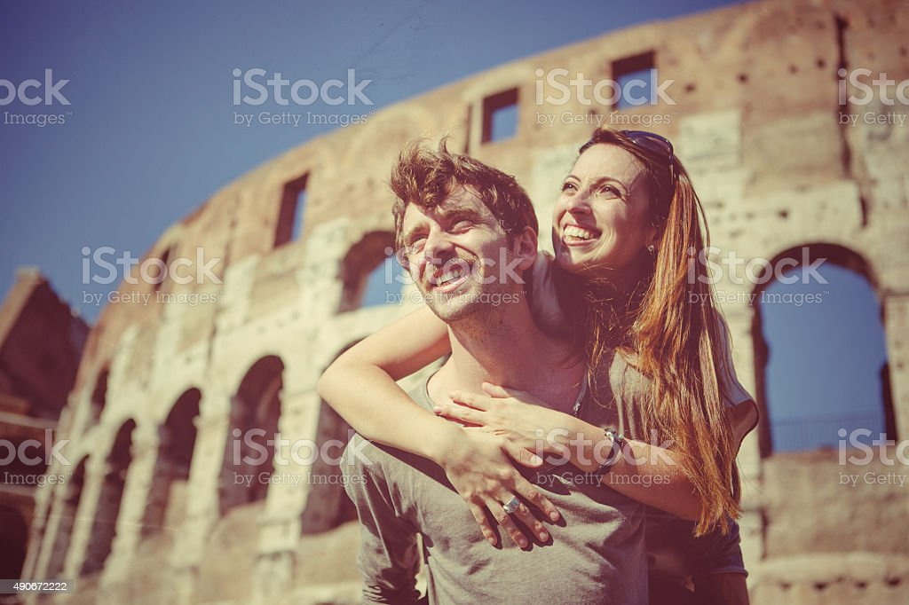 Couple piggyback in front of the Coliseum stock photo