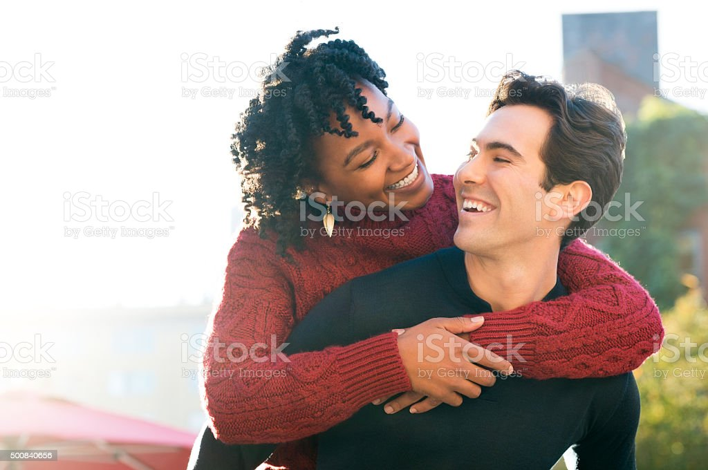 Couple piggyback outdoor stock photo