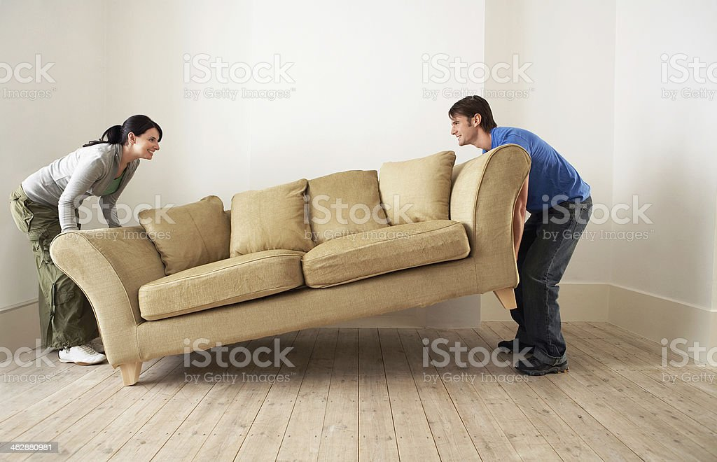Couple Placing Sofa In Living Room Of New Home stock photo