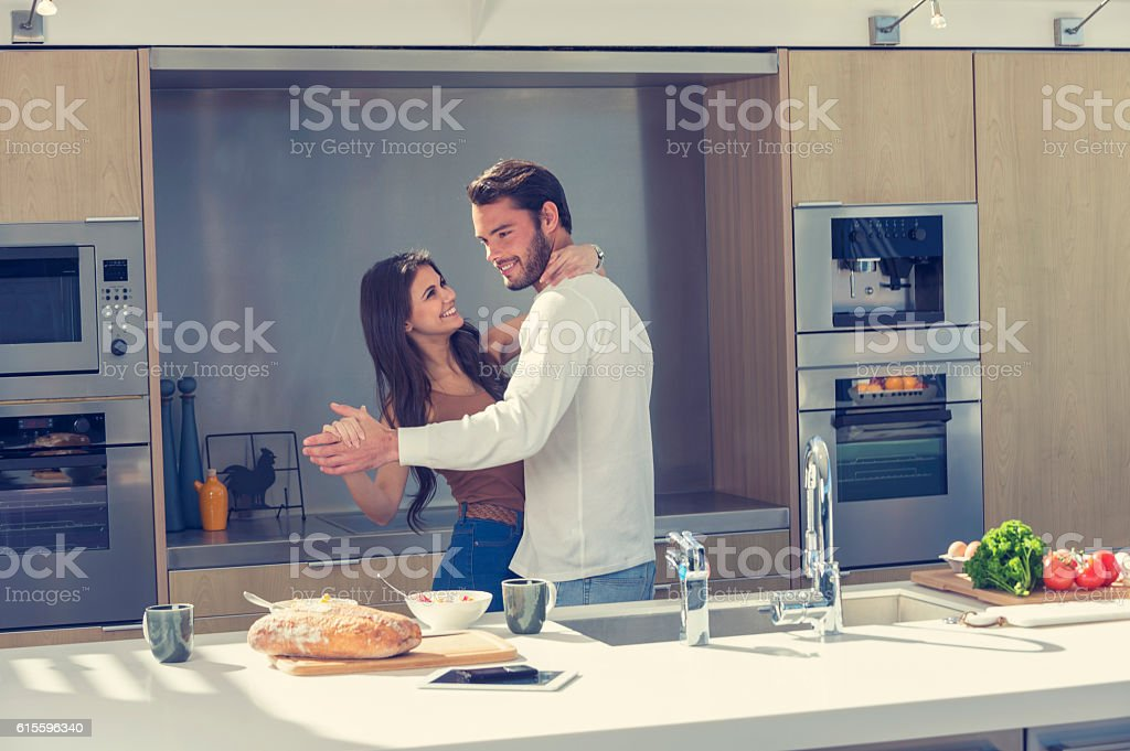 Couple playfully dancing in the kitchen. stock photo