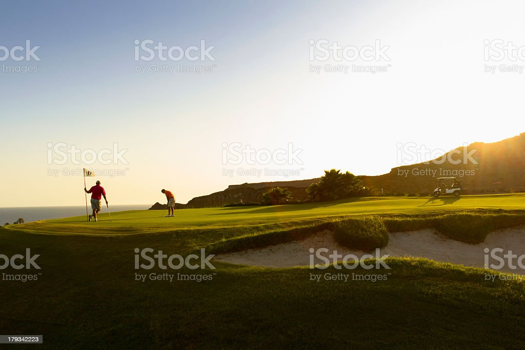 A couple playing golf on a putting green stock photo