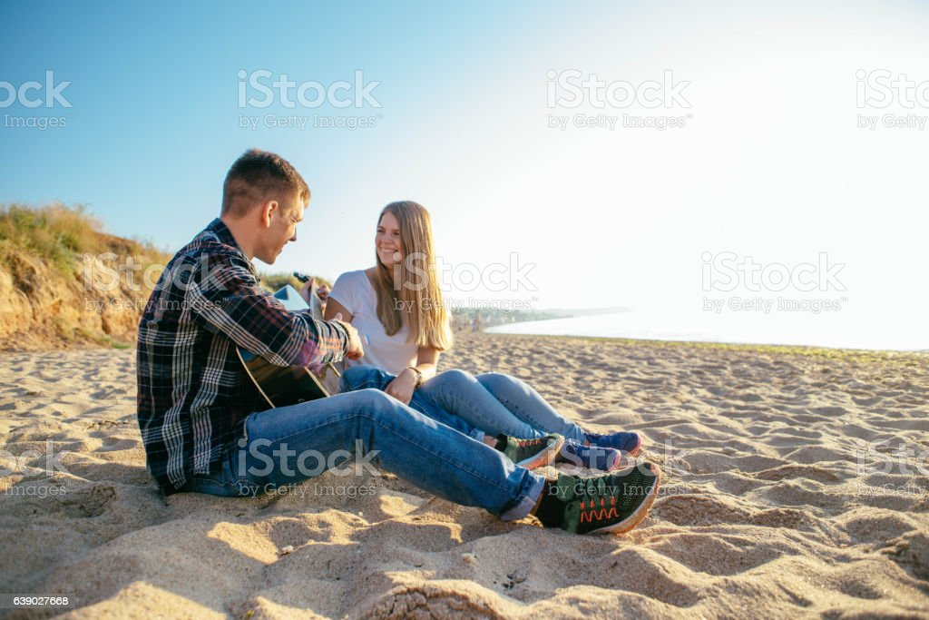 couple playing guitar on beach stock photo