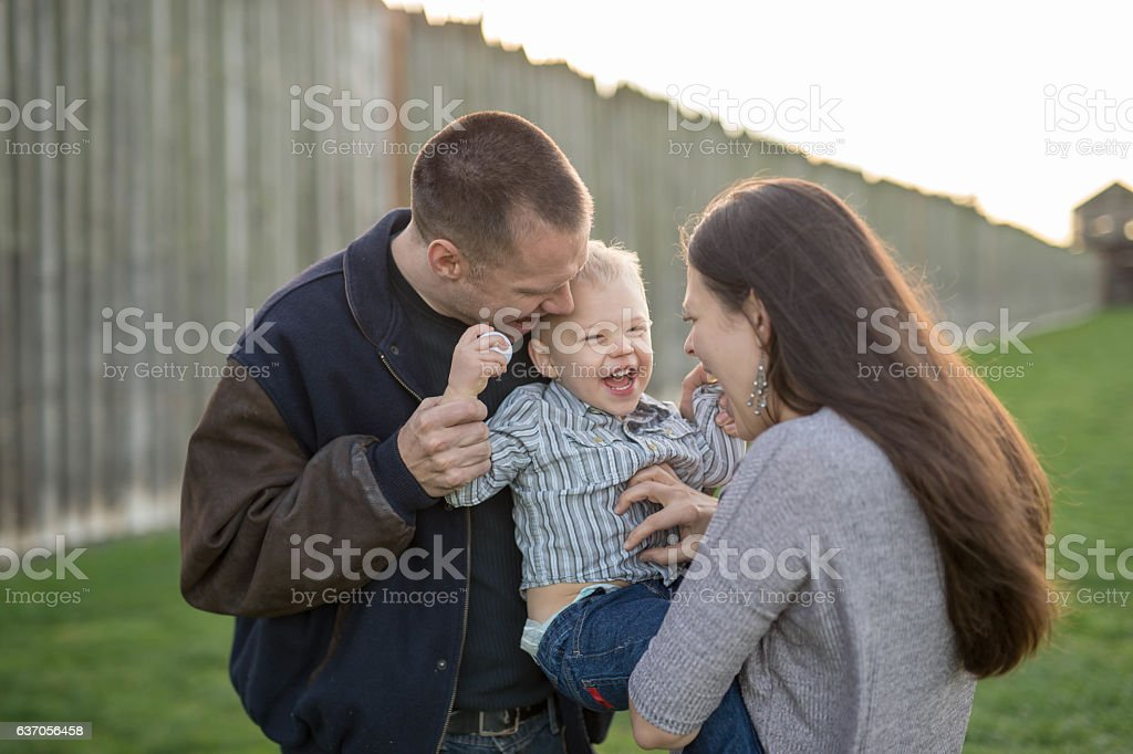 Couple playing in the park with their toddler son stock photo