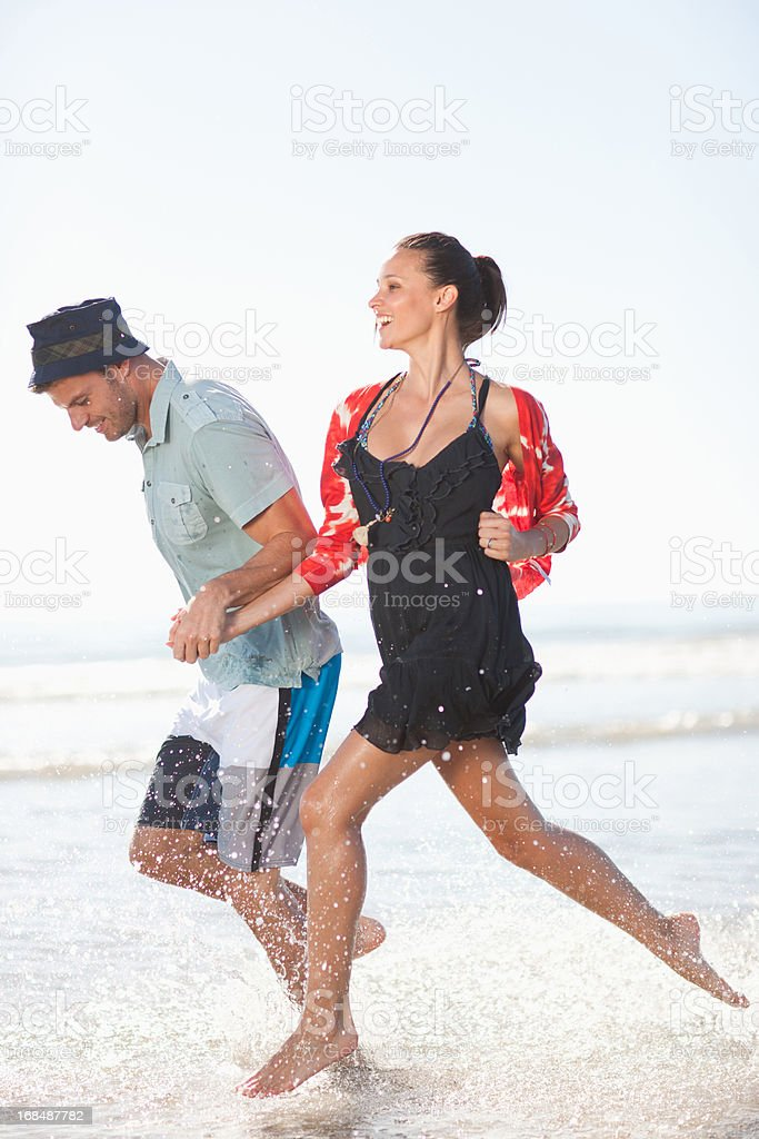 Couple playing in waves on beach royalty-free stock photo