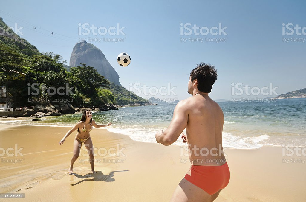 Couple playing soccer on beach royalty-free stock photo
