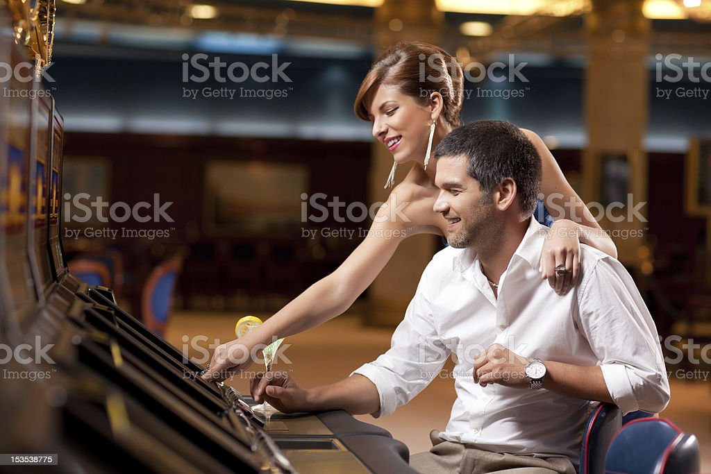 A couple playing the slot machine in a casino royalty-free stock photo