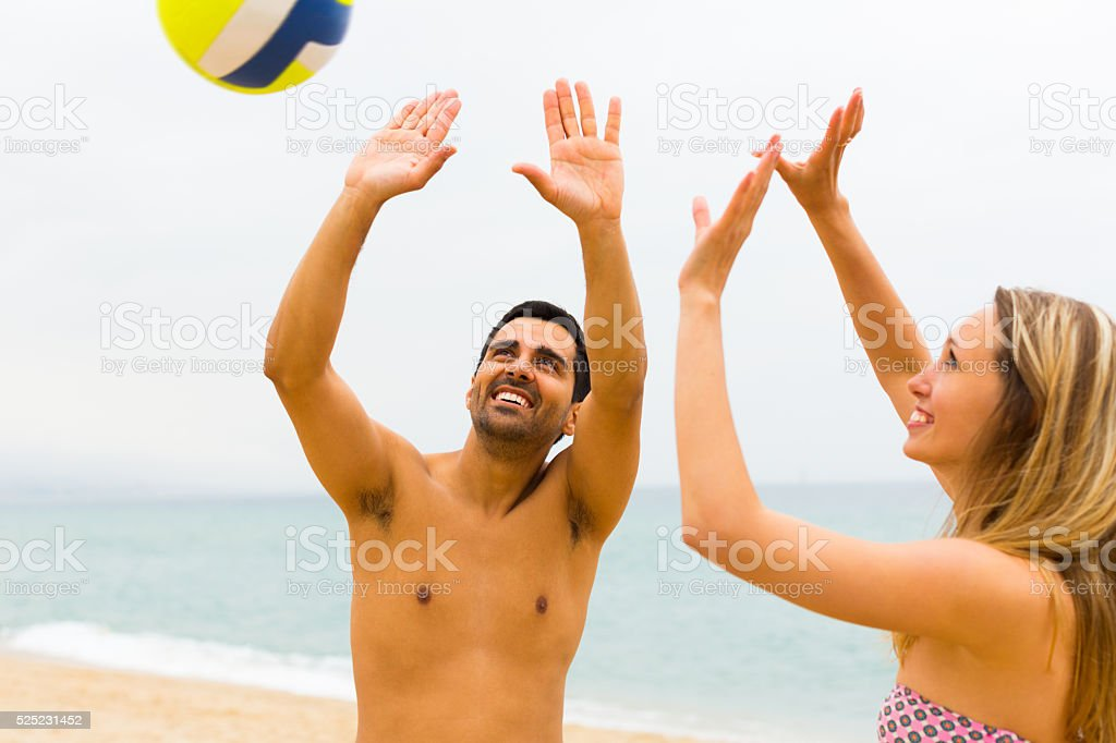 Couple playing with a ball on the beach stock photo