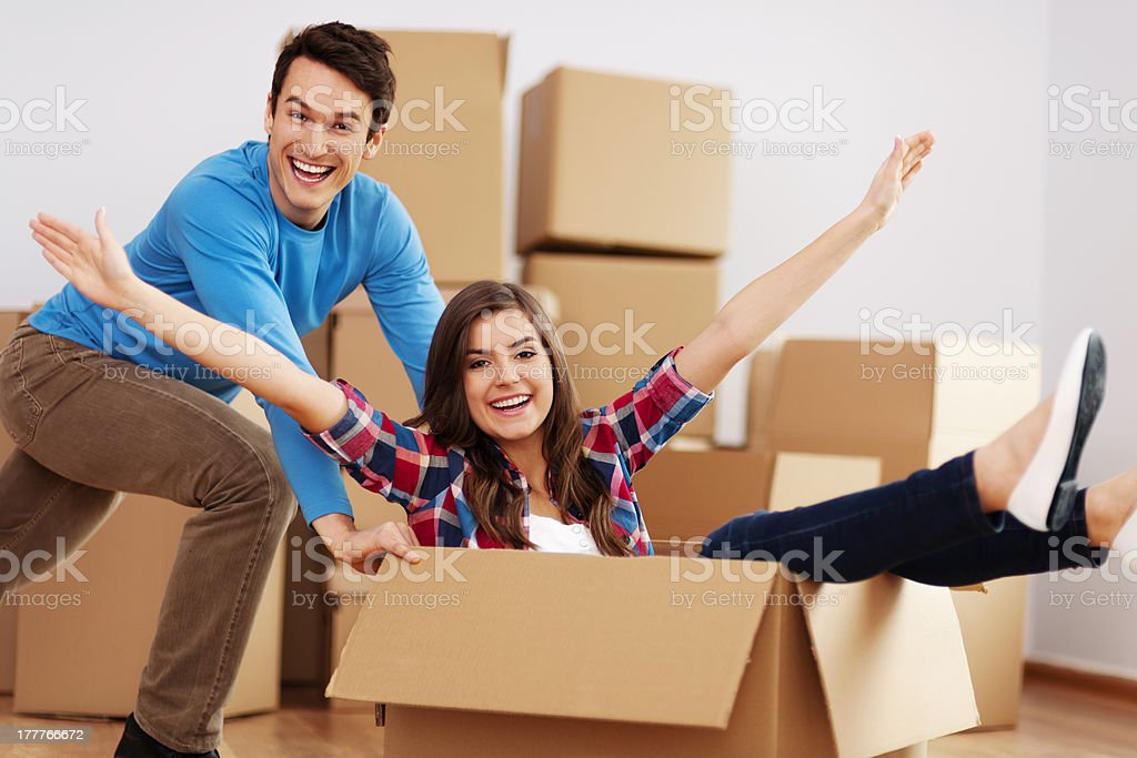 Couple playing with box in their new home royalty-free stock photo