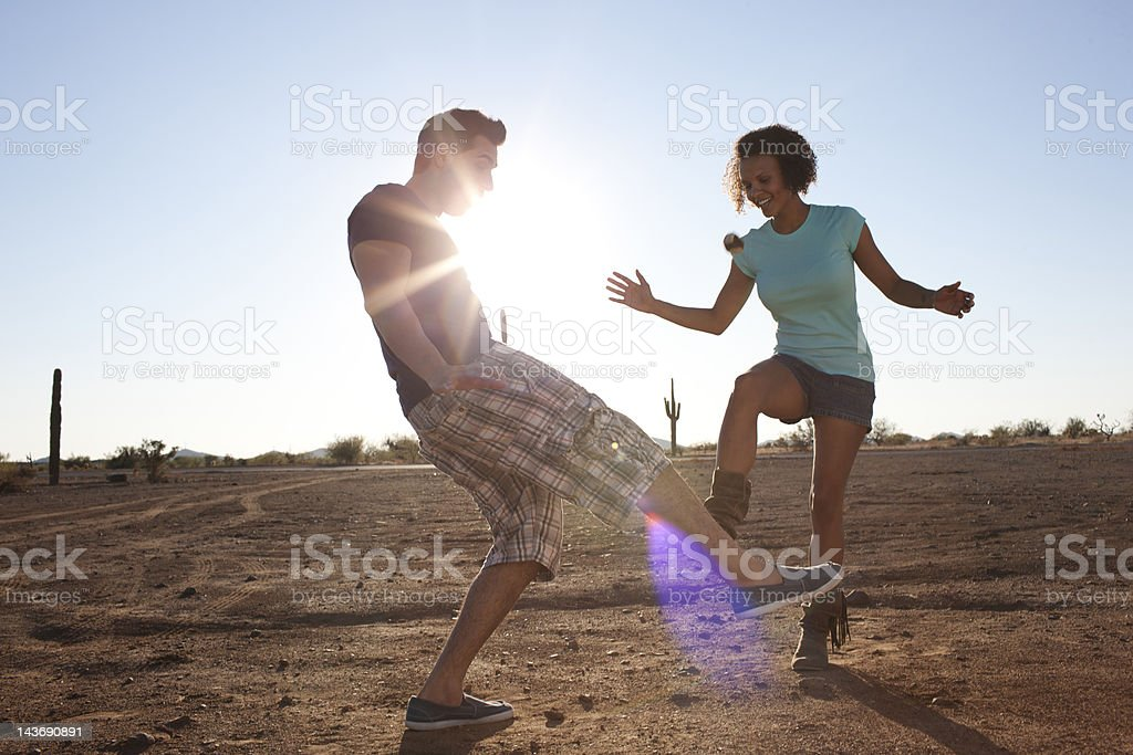 Couple playing with hackey sack outdoors stock photo