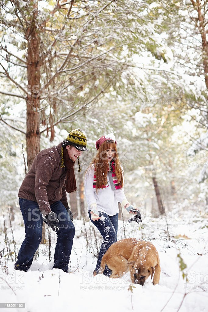 Couple playing with their pet in snowy winter scene stock photo
