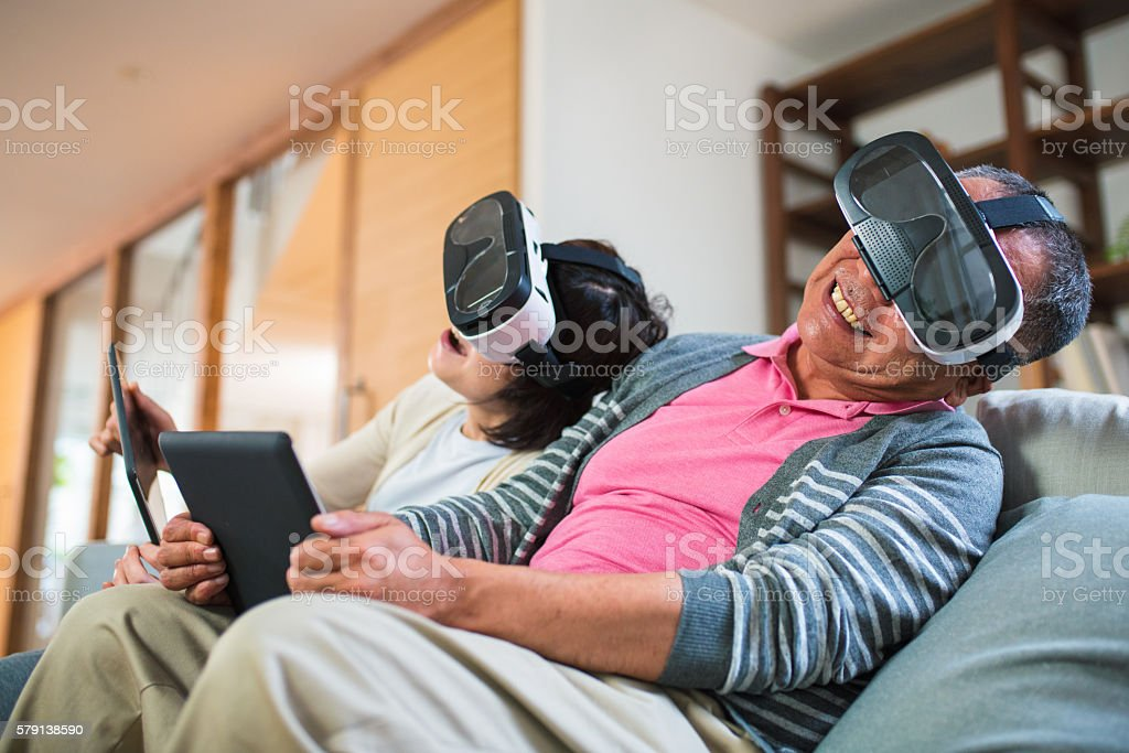Couple playing with virtual reality headsets stock photo