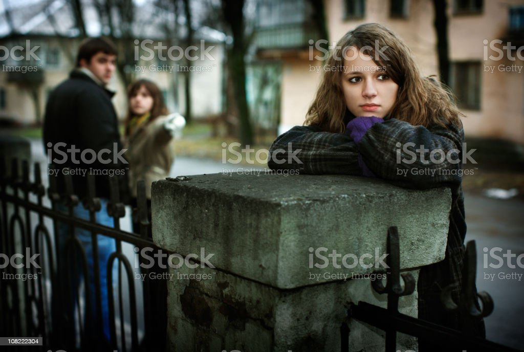 Couple Points at Sad Young Woman Leaning on Fence royalty-free stock photo