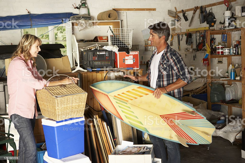 Couple preparing food and surfing board for beach holiday stock photo