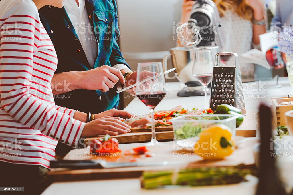 Couple preparing pizza, close up of hands stock photo