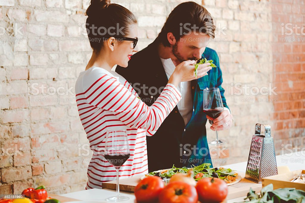Couple preparing pizza in the modern kitchen, drinking wine stock photo