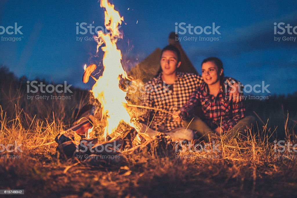 Couple preparing sausages on bonfire stock photo