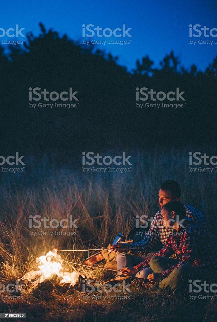 Couple preparing sausages on bonfire stock photo