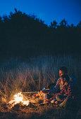 Couple preparing sausages on bonfire