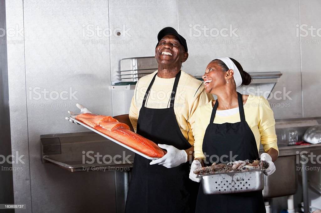 Couple preparing seafood in back room of fish market stock photo