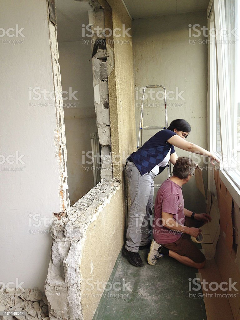 Couple Protecting Balcony During Home Addition Europe royalty-free stock photo