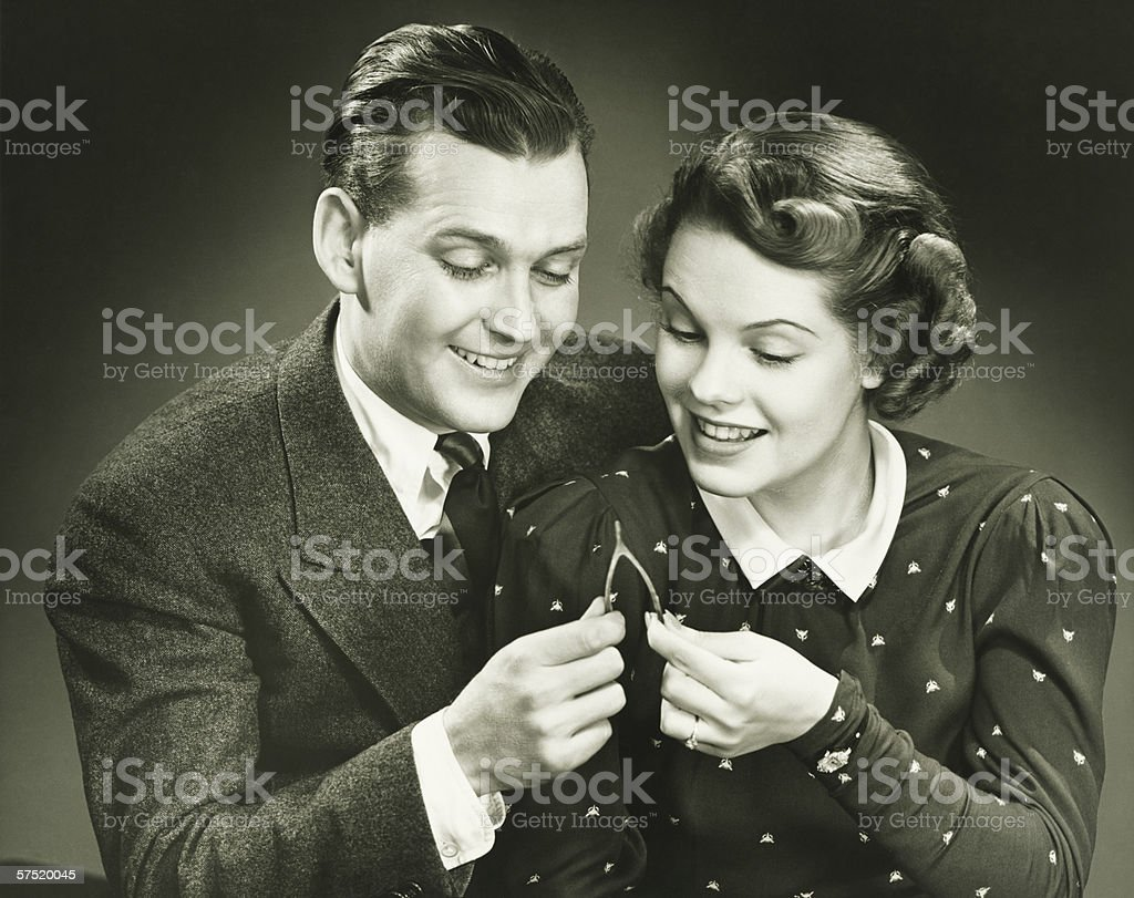 Couple pulling wishbone in studio, (B&W), close-up, portrait stock photo